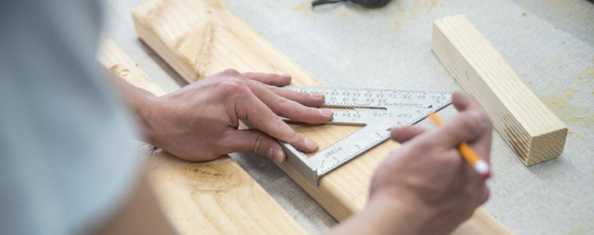 hands marking 2x4 pieces with ruler and pencil
