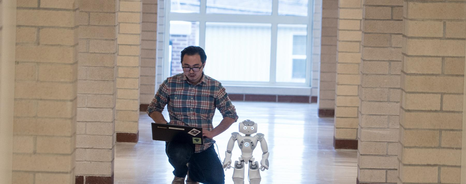student with robot in hallway