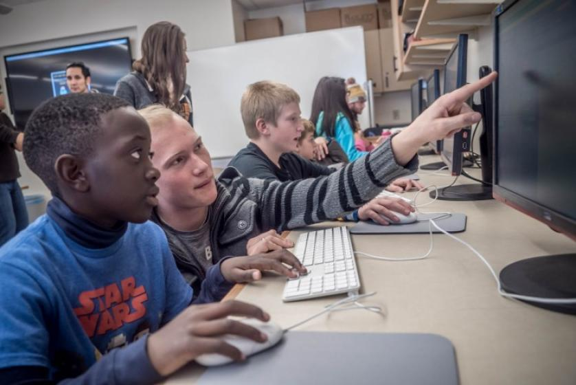 College and elementary students work together on computer